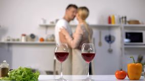 Wine glasses on table, family couple dancing on background, kitchen interior royalty free stock photos