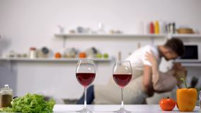 Wine glasses on table, girlfriend and boyfriend dancing on background, love royalty free stock image