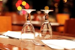 Wine glasses and table setting in a parisian restaurant. Table setting with glass at a restaurant, in a Parisian bistro, and napkins in front of abstract blurred stock photography