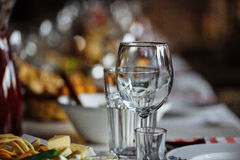 Wine glasses and table setting in restaurant. One empty wine glass and water glass and table setting in modern cozy restaurant Royalty Free Stock Image