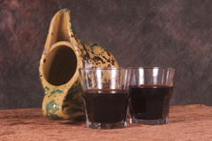 Wine glasses, terracotta jar. Closeup of two small glasses with red wine and a terracotta jar nearby stock image