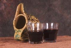 Wine glasses, terracotta jar. Closeup of two small glasses with red wine and a terracotta jar nearby Stock Image