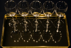 Wine Glasses on Tray. Wine glasses reflect and sparkle on a mirrored tray; black background Stock Photo