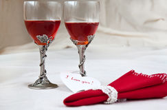 Wine glasses and Valentine heart. Two beautiful glasses with red napkin, heart and rose Royalty Free Stock Photography