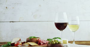 Wine glasses and various tapas on wooden board. Close-up of wine glasses and various tapas on wooden board stock footage