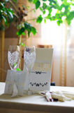 Wine glasses, wedding card with ribbons and an invitation to the table Stock Images