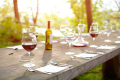 Wine glasses on a wooden table in the countryside shallow depth royalty free stock images