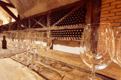 Wine glasses on wooden table of the tasting room of old cellar Royalty Free Stock Photography