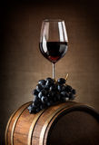 Wine goblet and barrel. Wine goblet with wooden barrel and grape royalty free stock photos