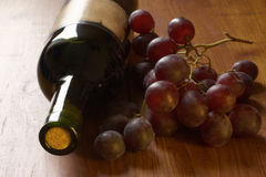 Wine and grape. Wine bottle and grape lying on wood surface. Selective focus on foreground Royalty Free Stock Photos