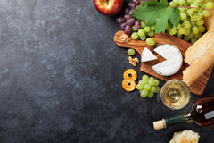 Wine, grape, cheese. White wine, grape, bread and cheese on stone table. Top view with copy space Royalty Free Stock Photography