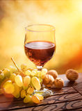 Wine and grape with walnuts on wooden table Royalty Free Stock Images