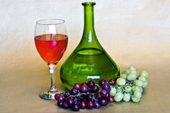 Wine and grapes. A still life of a bottle of  wine and a glass of  wine and two bunches of grapes Stock Photo
