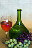 Wine, bottle and grapes. A still life of a bottle of  wine and a glass of  wine and two bunches of grapes Stock Photography