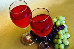 Wine and grapes. Two glasses of red  wine and two bunches of grapes Stock Image