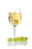 Wine and grapes. Wine in a glass with grapes, isolated on a white background. One grape plunges into the glass Stock Images