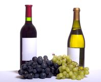 Wine and grapes. A bottle of red and white wine with blue and white grapes, on white Royalty Free Stock Image