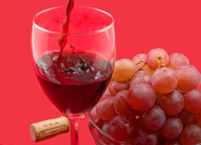 Wine and grapes. Red wine, red grapes in glass bowl on red background Royalty Free Stock Photos