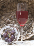 Wine with grapes. Wine in a glass. A glass standing against a wattled basket. Nearby there is a glass with grapes Royalty Free Stock Images