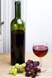 Wine and grapes. A bottle of red wine with filled glass and fresh grapes on wooden table royalty free stock photos