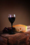 Wine grapes and cheese. Still life on brown background. Glass and food on wood box or crate Stock Photo
