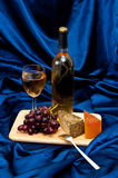 Wine grapes and cheese on satin Royalty Free Stock Image