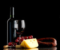 Wine, grapes, cheese and sausage on black background. Wine in bottle and glass, grapes, cheese an sausage on black background Royalty Free Stock Image