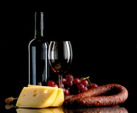 Wine, grapes, cheese and sausage on black background Stock Photo