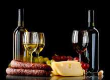 Wine, grapes, cheese and sausage on black background. Wine in bottle and glass, grapes, cheese an sausage on black background Stock Photos