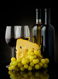 Wine, grapes and cheese. Still life with wine grapes and cheese on a black background Stock Photos