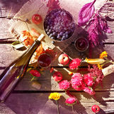Wine, grapes and flowers on grungy wooden table. Royalty Free Stock Photos
