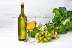 Wine and grapes. Glass and bottle of white wine with grapes on a wooden table Stock Photography