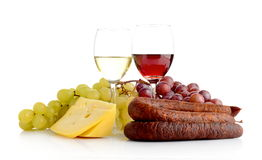Wine and grapes isolated on white with cheese and sausage. Red and white wine in wineglasses, two bunches of grapes, cheese and sausage isolated on white Stock Photography