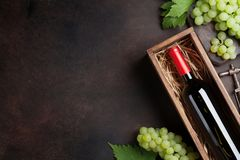 Wine and grapes. Red wine bottle in box and grapes on stone table. Top view with space for your text Royalty Free Stock Photo