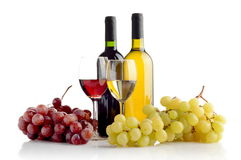 Wine and grapes  on white. Red and white wine in bottles and wineglasses and two bunches of grapes  on white Stock Photos