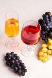 Wine and grapes. White and red wine in glasses on light marble b Royalty Free Stock Photo