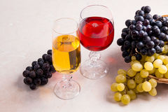 Wine and grapes. White and red wine in glasses on light marble b Royalty Free Stock Photography