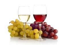 Wine and grapes  on white. Red and white wine in wineglasses and two bunches of grapes  on white Stock Photo