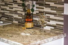 Wine, Holder & Glasses On Modern Kitchen Counter royalty free stock image
