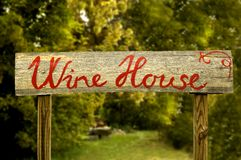 Wine house. Writing on a wooden board with green blur background Stock Image