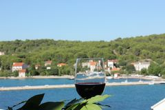 Wine IMG_9121. Glass of wine and laurel branch with mediterranean village in background, island Zlarin, Croatia stock images