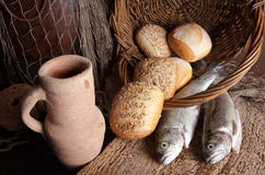 Wine jug with bread and fish Stock Photos