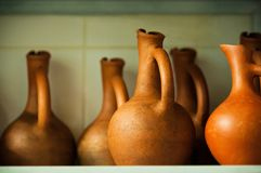 Soft focused wine jugs of terracotta color on the rack. Wine jugs of terracotta color on the rack, closeup view, soft focus Royalty Free Stock Images