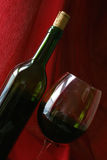 Wine Life 7. Wine bottle and glass angled against red drape Royalty Free Stock Photos
