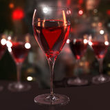 Wine for a lonely heart. A glass of red wine with a heart. Blurred background Royalty Free Stock Image