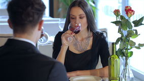 Wine and loved ones. Romantic dinner in the restaurant. Young couple sitting at a table at each other and smiling lovingly at the restaurant while toasting stock video