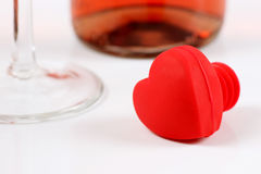 Wine Lover. Bright red heart-shaped wine stopper with wine bottle and stemwear on white Royalty Free Stock Image