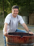 Wine maker. Young man standing by the wooden barrel Royalty Free Stock Images