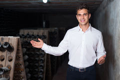 Wine maker in cellar with wine bottles storage Stock Photos