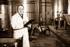 Wine maker examines equipment at winery Royalty Free Stock Photo